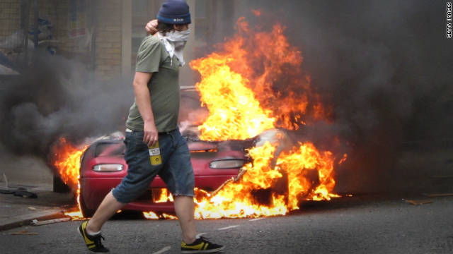 A masked man walks past a burning car outside a Carhartt store in Hackney on August 8, 2011 in London, England.
