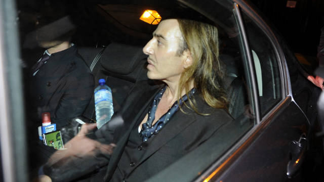 """This June 22, 2011 file photo shows fashion designer John Galliano as he leaves in a car after he stood trial for anti-Semitic insults in a Paris' court. John Galliano, the flamboyant fashion designer who fell from grace after an anti-Semitic outburst in Paris, has said making supermodel Kate Moss' wedding gown this summer was his """"creative rehab."""""""