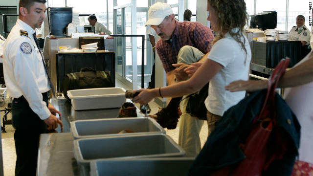 A passenger takes off his shoes at a security check-point at Dulles International Airport .