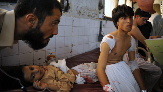 Local residents chat with wounded school children at a hospital following an ambush by gunmen in Peshawar.