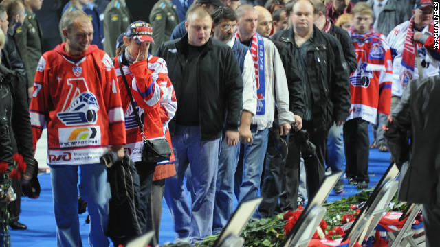People mourn in front of the portraits of victims during a memorial ceremony for those killed in the Russian ice hockey team Lokomotiv Yaroslav plane crash at Arena-2000 the team's stadium in Yaroslavl on September 10, 2011