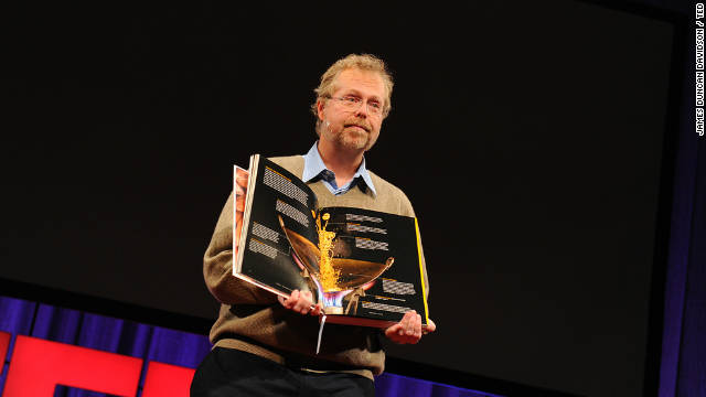 Nathan Myhrvold holds up his $625, 2,400-page book on the art and science of cooking, at TED2011 conference.