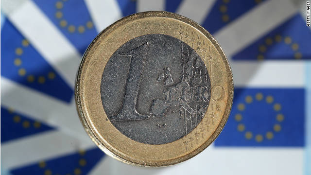 In this photo illustration a 1 euro coin sits on a display European Union flags.