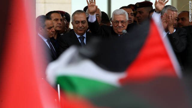 Palestinian President Mahmoud Abbas waves to Palestinians as they welcome him at his Ramallah headquarters Sunday.