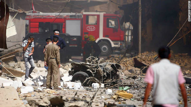Iraqi police and firefighters inspect the scene following an explosion in the central Iraqi shrine city of Karbala.