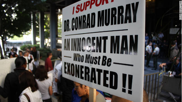 Supporters of Conrad Murray wave signs outside the courthouse.
