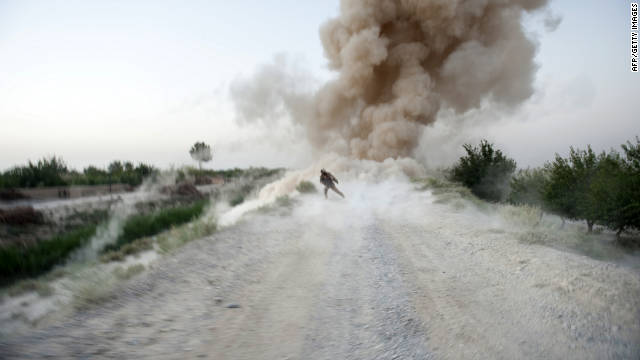 A U.S. Marine takes covers as an IED detonates in Helmand province, Afghanistan.