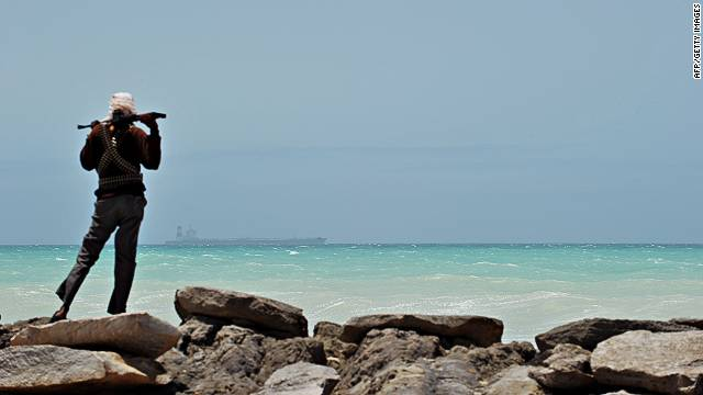 A pirate stands on a rocky outcrop on the coast of Hobyo, central Somalia.