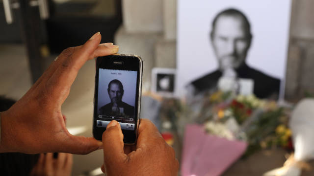 A man uses an iPhone to photograph a memorial to Steve Jobs outside an Apple Store in London.