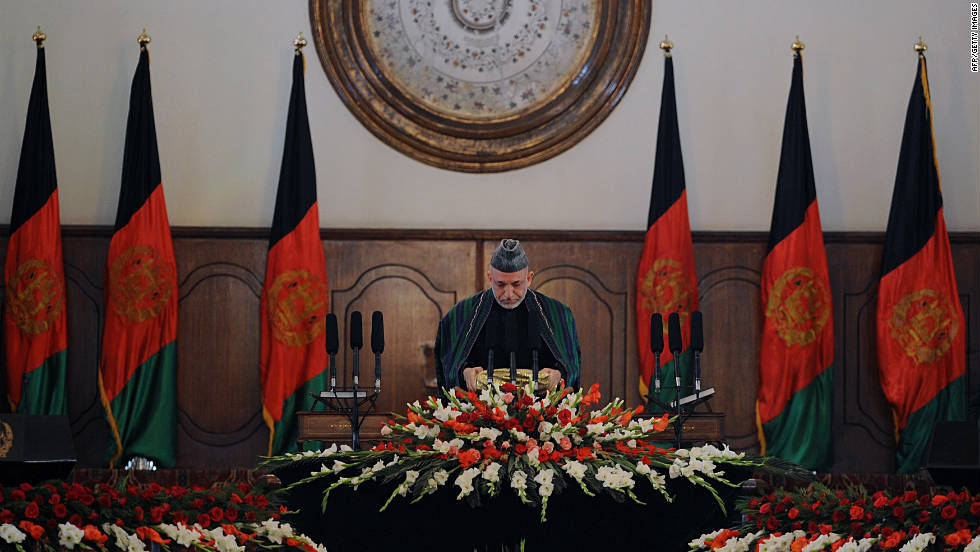President Karzai prepares to kiss a large copy the Quran during his swearing-in ceremony in Kabul on November 19, 2009.  He was elected to a second term by default when Foreign Minister Abdullah Abdullah dropped out of the race and the run-off election was canceled.