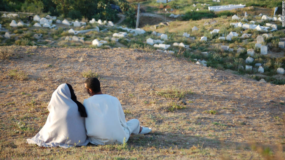 "Marc Burba felt compelled to snap a shot of this couple in Fez. ""A young couple enjoys the sunset from the Borj Nord Hill. An old cemetery is below them."""