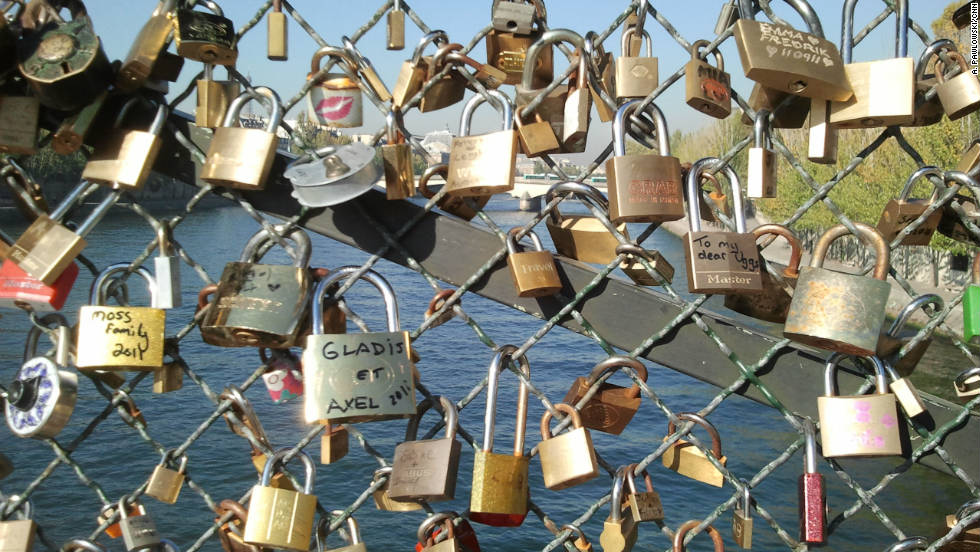 Lovers leave locks inscribed with their names on Pont des Arts.