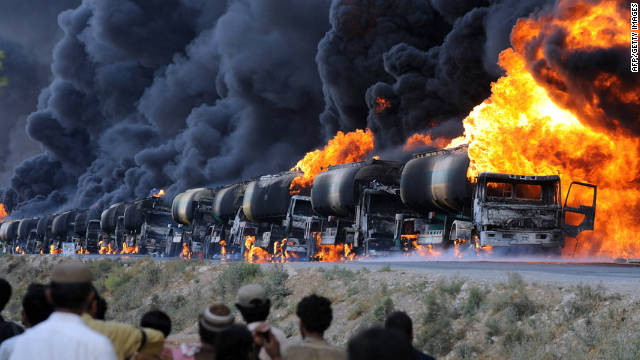 The burning remains of a NATO supply convoy symbolizes the immense threat from Taliban insurgents.