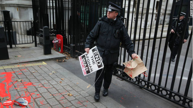 A policeman at Downing Street, London, clears away placards left by an anti-war protest on the 10-year anniversary.