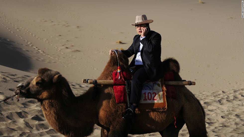 A Chinese tourist talks on his phone while riding a camel through the sand dunes in China's northwest Gansu province on September 27, 2008. Low-cost cell phone towers allows mobile coverage in ever more remote locations.