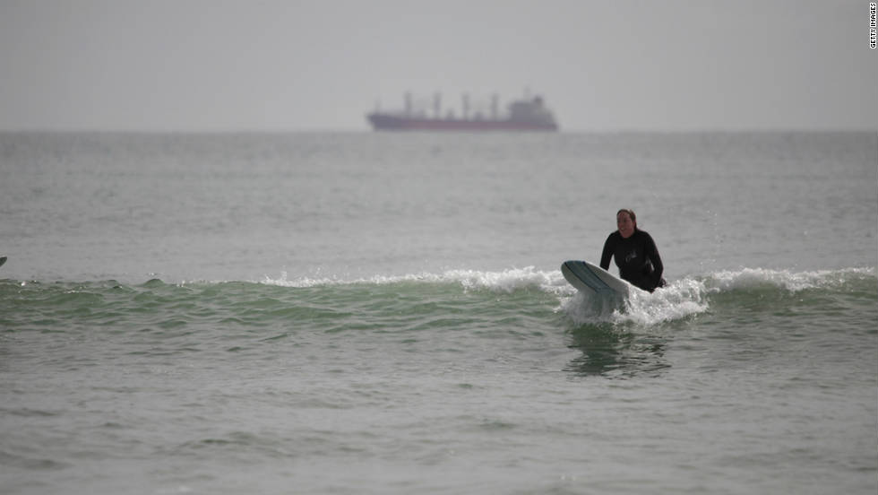 A surfer catches a wave with the main cargo route in the background near the port of Tauranga on October 8.