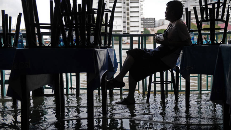 A Thai employee of a riverside restaurant sits idle as water from a river floods low-lying areas of Bangkok on October 4, 2011.