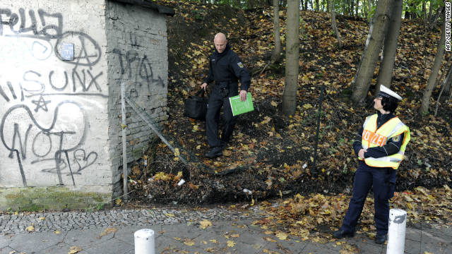 A policeman carries a bag after searching for evidence at a place where flammable devices were found.