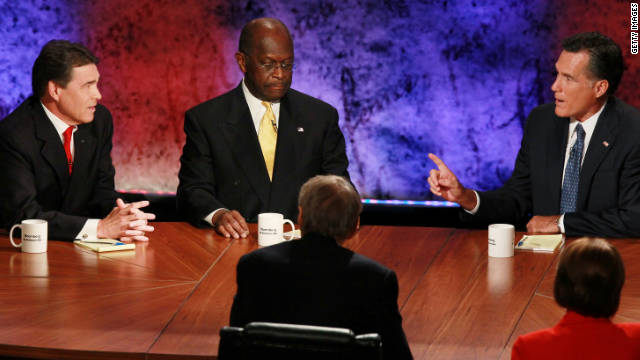 Mitt Romney, right, makes a point as Rick Perry, left, and Herman Cain listen at the GOP presidential debate October 11.