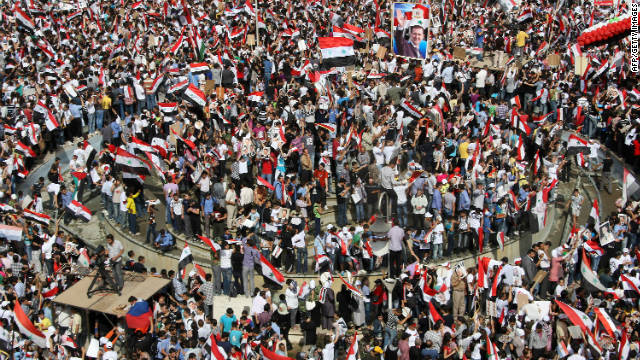 Supporters of Syrian President Bashar al-Assad wave Syrian flags during a pro-regime rally in Damascus on October 12.