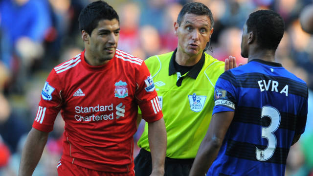 Referee Andre Marriner (C) talks to Liverpool's Luis Suarez (L) and Manchester United's Patrice Evra at Anfield on Saturday.