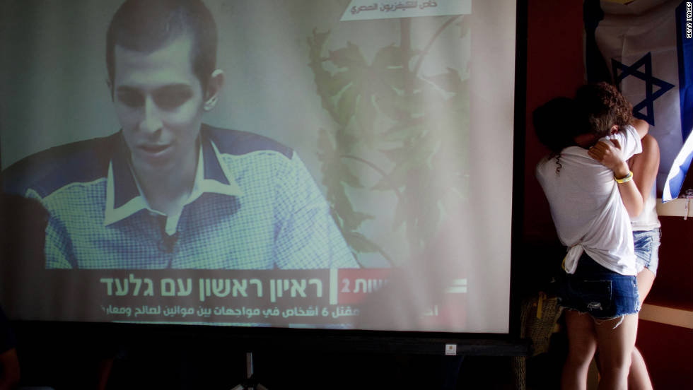 Israelis react after seeing the first images of Shalit on TV following his release.