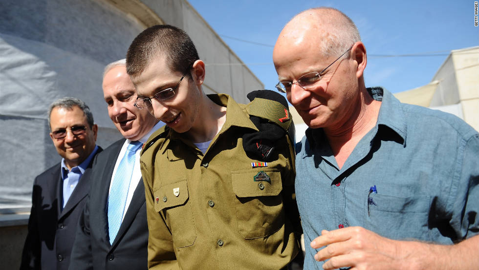 Israeli Defense Minister Ehud Barak, from left, Netanyahu, Gilad Shalit and his father, Noam Shalit, walk together at Tel Nof Airbase on Tuesday. Shalit was given medical checks that showed him to be in good health.