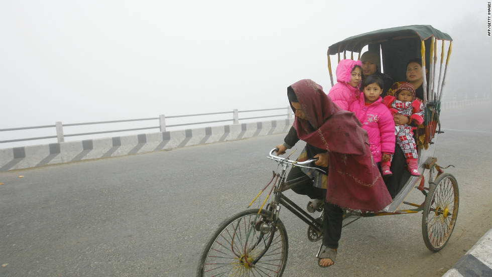 In Nepal, bicycles can be used to transport an entire family. Here, a Nepalese cycle rickshaw and passengers drive on a street of Chitwan, some 170 km south of Kathmandu.