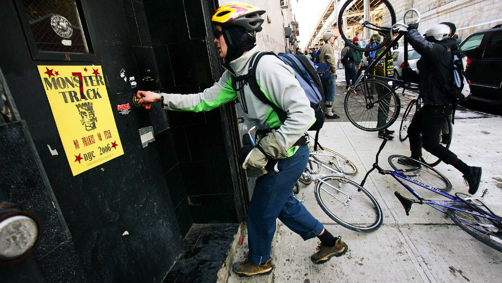 Monster Track is a well-known, illegal race through New York City for bike messengers that involves racing to checkpoints on bikes with no brakes. Here, a competitor opens a door at the end of the race.