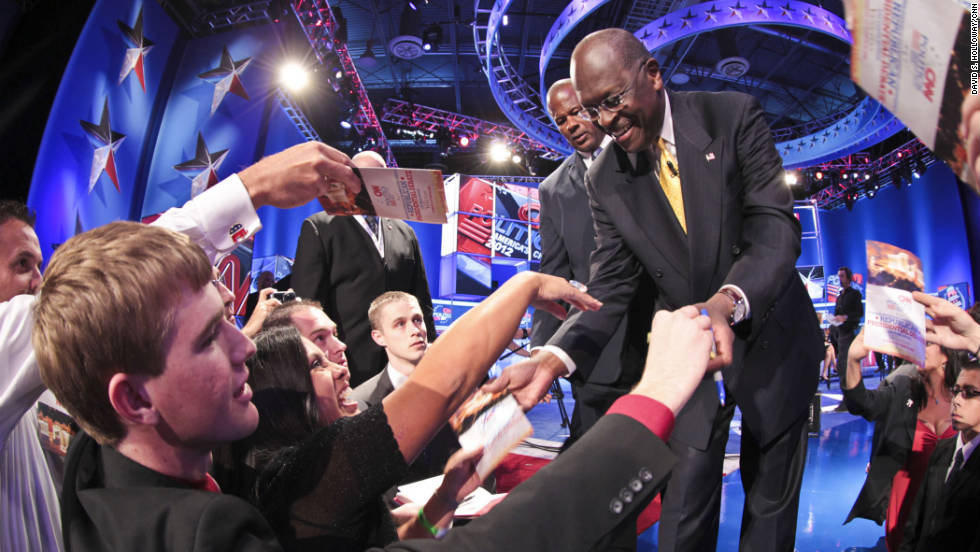Former Godfather's Pizza executive Herman Cain greets the audience.  GOP rivals took turns picking apart his 9-9-9 tax plan, which would throw out the current tax system and replace it with a 9% corporate income tax rate, a 9% income tax rate and a 9% national sales tax.