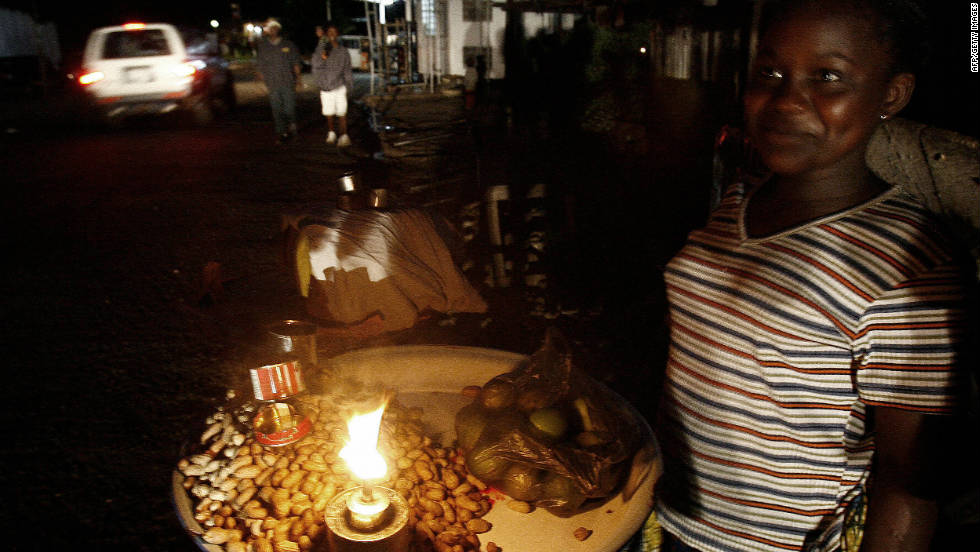 A street vendor lights her stand with a candle in July 2006 in Sierra Leone's capital, Freetown.