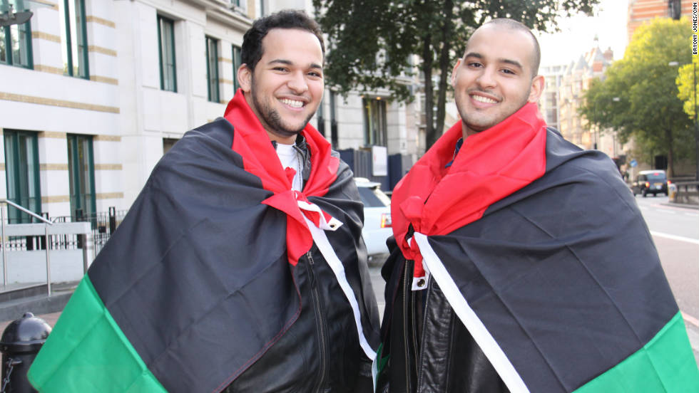 Two Libyan students wore their nation's new flags as capes when they joined in the party-like atmosphere at the embassy, in central London.