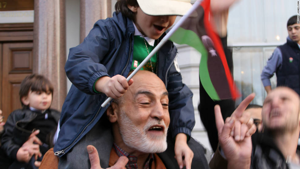 A man dances with a child on his shoulders outside the Libyan Embassy in London.
