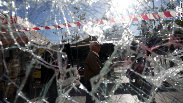 A man walks behind a broken storefront in Athens on October 20, 2011. Greece faced a critical austerity vote aimed at averting a debt default as protestors rallied for a second day after violence injured dozens on the opening day of a 48-hour general strike.