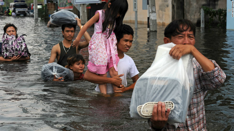 Thai people carrying their belongings wade through floodwaters as they evacuate the inundated Ban Bua Thong district of Nonthaburi province, suburban Bangkok on October 20.