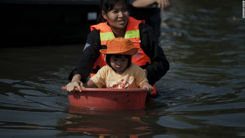 A Thai rescuer holds afloat a girl inside a plastic bowl in floodwaters as water levels rose after a mud and sandbag wall collapsed in Bang Bua Thong in Nonthaburi province, suburban Bangkok, on October 19.