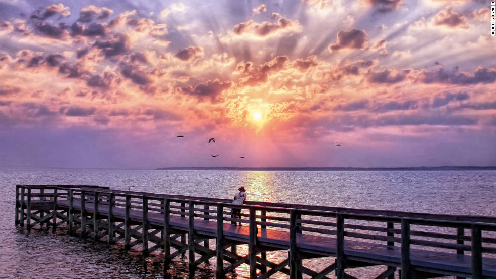 "Xynn Tii took this photo of a sunrise over Gulf Breeze. ""As a fisherman approached the boardwalk, he put down his gear and enjoyed the sunrise for a couple minutes. His solitude really complemented the scene as he and I witnessed a glorious daybreak."""
