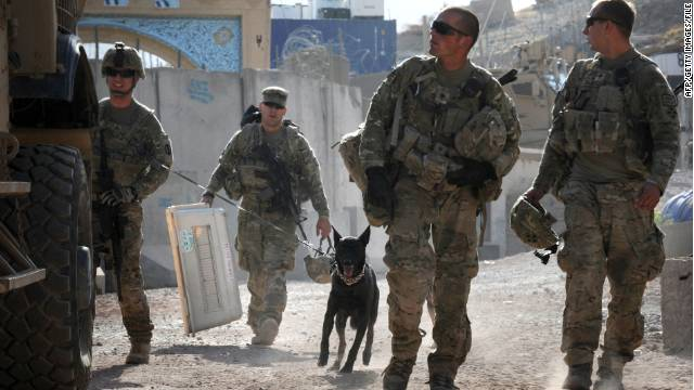 This photograph taken July 25, 2011 shows US Army Sergeant Nathan Arriaga (L) of the US Forces Afghanistan K-9 unit, walking with Zzarr, a 6-year old Dutch Shepherd at the Forward Operating Base Walton,  on patrol mission with 1st Battalion 67th Armoured Regiment, Task Force Dealers in the Arghandab district. Zzarr who has a rank of Staff Sergeant is a military working dog trained to detect bombs and improvised explosive devices (IED) and currently deployed in southern Afghanistan saving lives of coalition forces in its war against Taliban insurgents. Both Zzarr and K-9 handler Sgt. Arriaga did their first combat duty in Iraq in 2009. AFP PHOTO / ROMEO GACAD (Photo credit should read ROMEO GACAD/AFP/Getty Images)