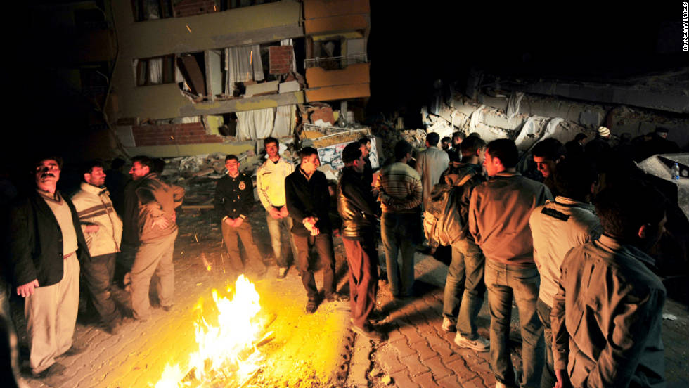 Ercis residents gather around a fire in the street and survey the destruction of the surrounding city on Sunday.
