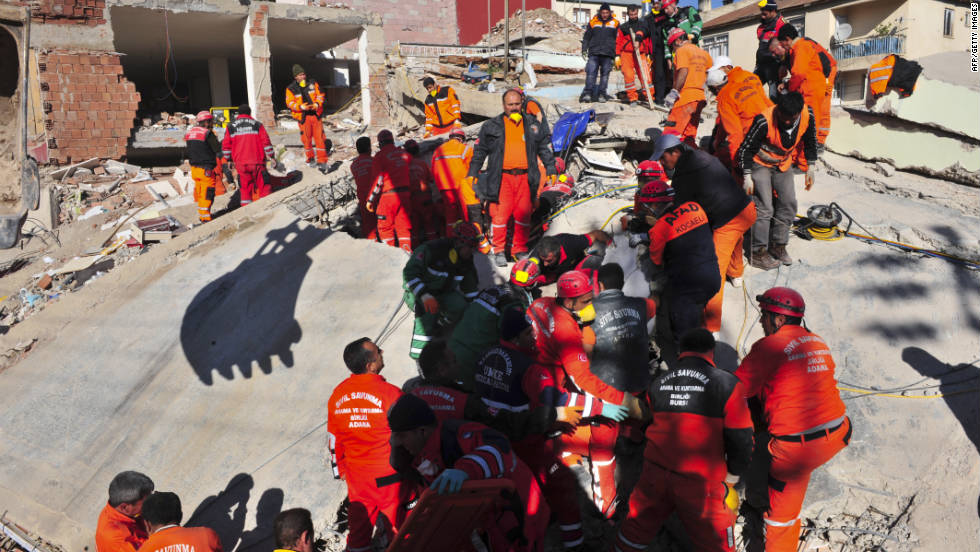 Turkish rescue workers try to recover people from a collapsed building in Ercis on Monday.