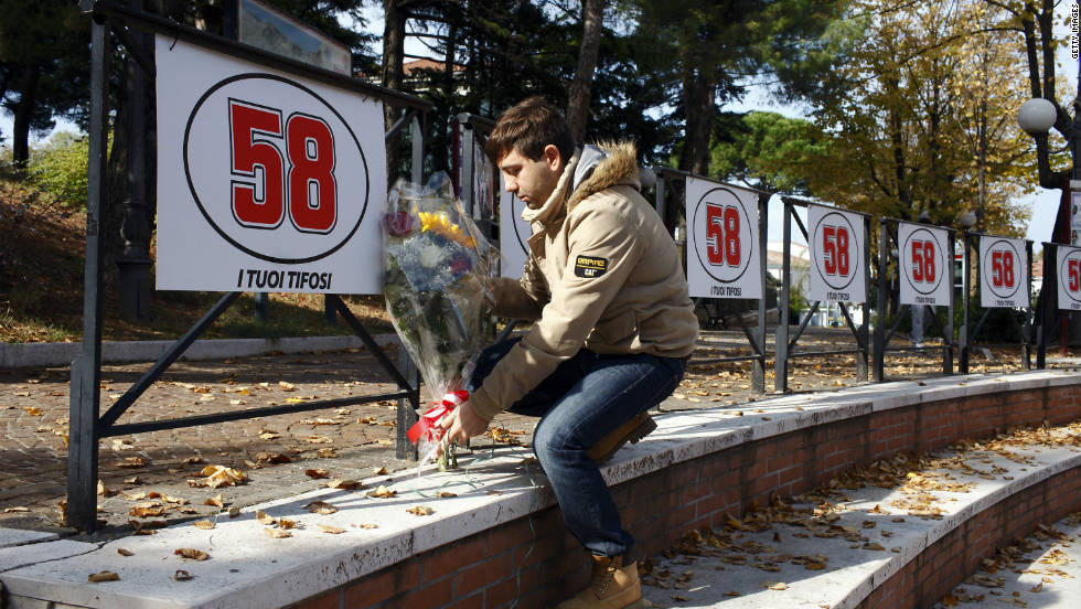 An Italian MotoGP fan lays flowers under Simoncelli's race number in the town of Cattolica.
