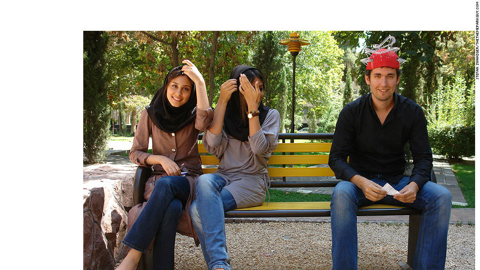 Theme park expert, Stefan Zwanzger, wearing his trademark roller coaster hat, sits next to some young Iranian women.