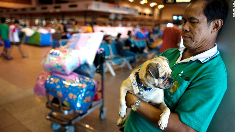 A man holds his dog and stands by his belongings at the Don Muang airport. He's waiting to be transferred to a new evacuation center.