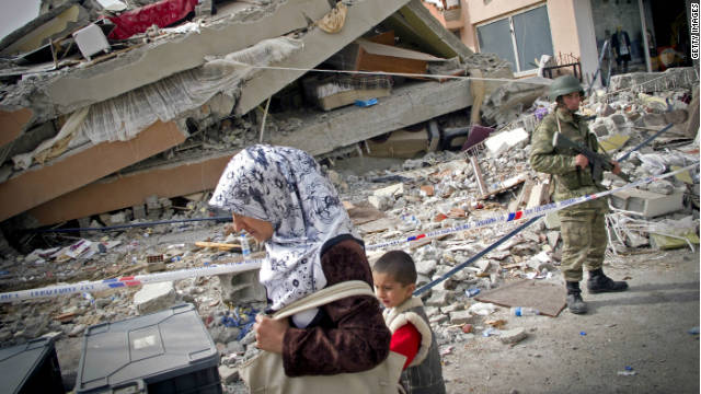 A woman and child walk past a collapsed building, as a soldier stands guard after the earthquake.