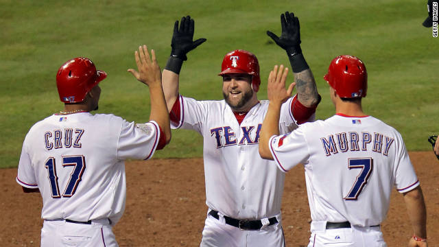Texas Rangers Nelson Cruz, left, Mike Napoli and David Murphy celebrate during Game Four of the World Series.