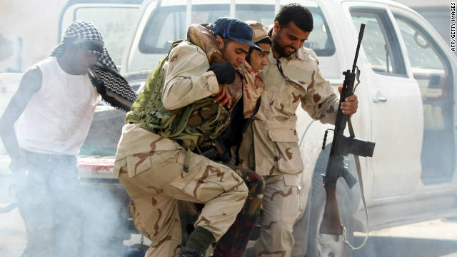 Libyan NTC fighters take a wounded comrade to a field hospital in Sirte on October 18.