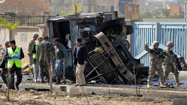 Afghan security forces and NATO troops inspect the site of a suicide attack in Kabul on Saturday.