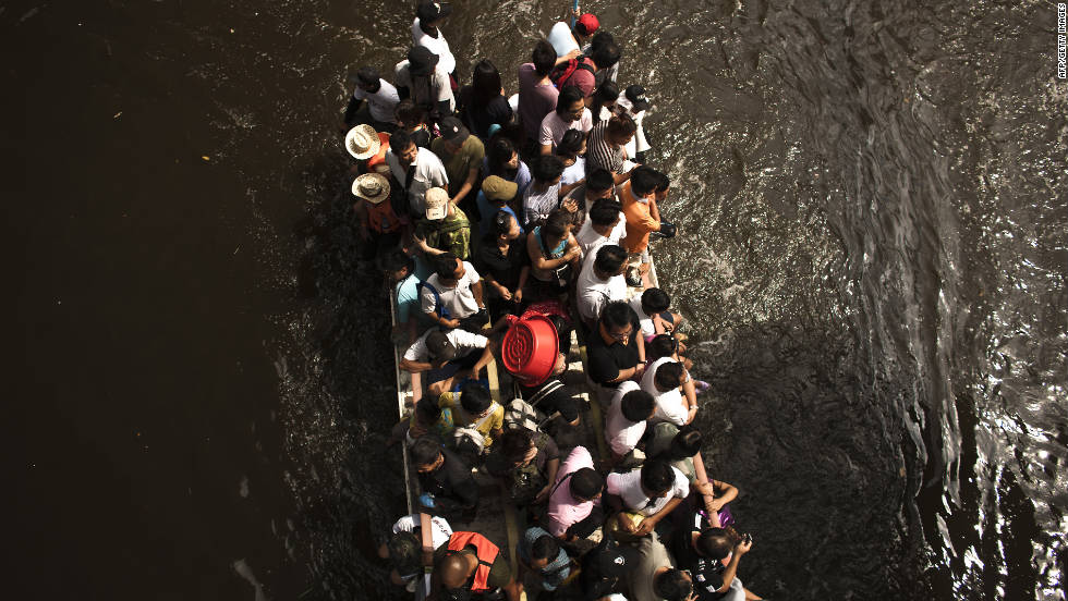 People travel on a truck along a flooded street on Sunday in Bangkok.