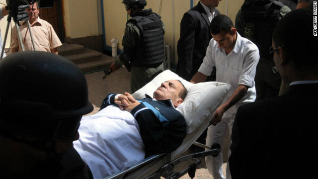 Ousted Egyptian president Hosni Mubarak lies on a stretcher as he is wheeled into a courtroom in Cairo on September 7, 2011.