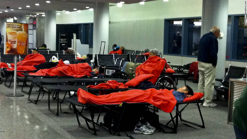 JetBlue passengers stranded in Hartford, Connecticut, sleep on floors and cots at the airport. They had to line up to get new seats on their diverted flights.<br />